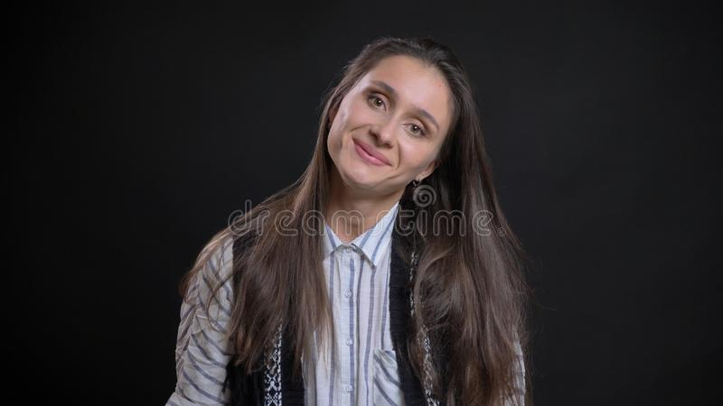 看照相机的年轻俏丽的白种人女性特写镜头画象微笑和倾斜她的头对边 免版税库存照片
