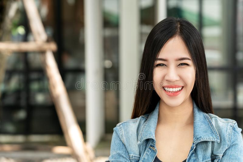 看照相机的年轻可爱的亚裔妇女画象微笑与确信和正面生活方式概念对室外咖啡馆 库存图片