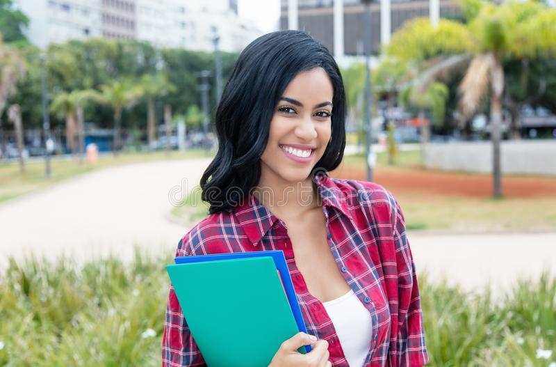 看照相机的当地拉丁美洲的女学生 免版税库存照片