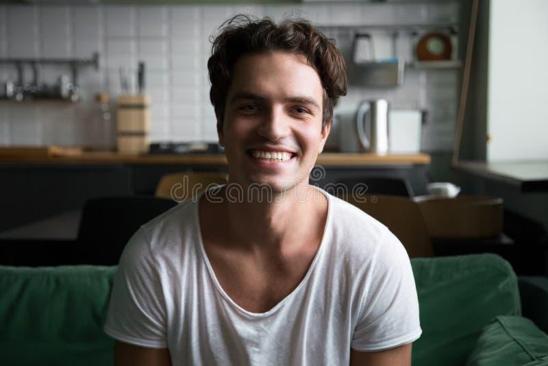 看照相机的微笑的人坐厨房沙发,画象 免版税库存照片