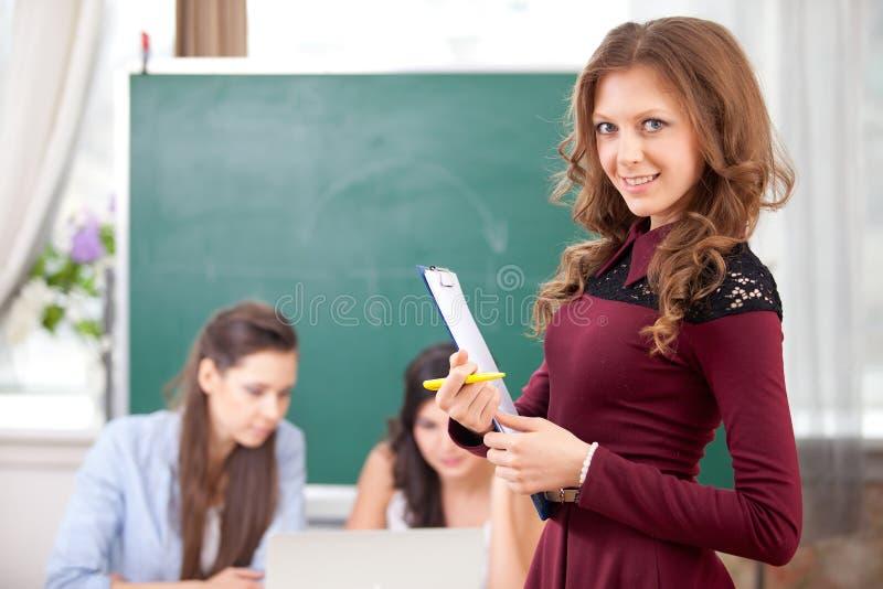 看照相机的微笑的俏丽的女孩在学院 图库摄影