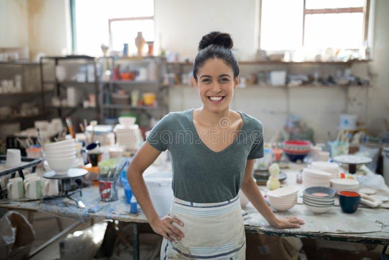 看照相机的微笑的俏丽的陶瓷工 图库摄影