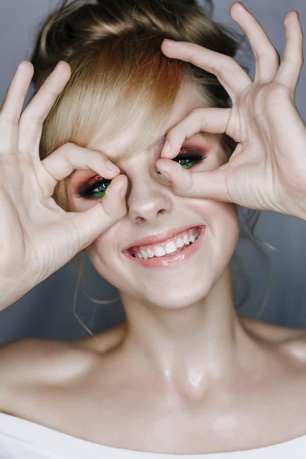 看照相机的微笑的妇女通过手指 图库摄影