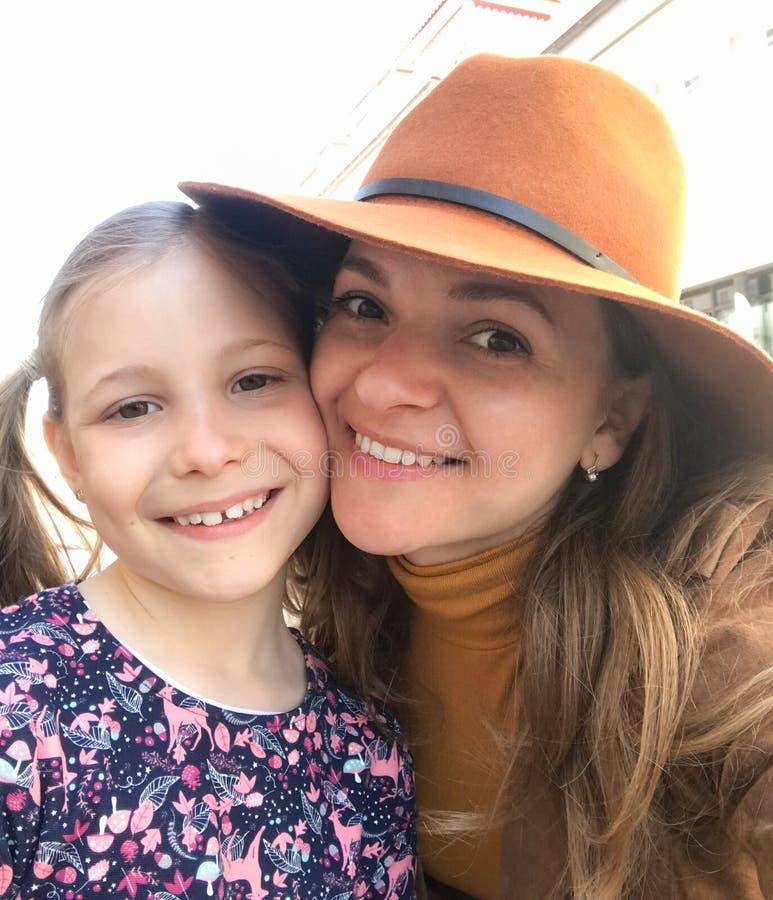 看照相机的微笑的母亲和女儿 免版税图库摄影