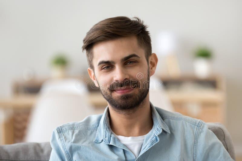 看照相机的微笑的男性画象在家坐 免版税库存照片