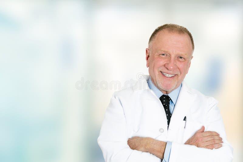 看照相机的微笑的资深医生站立在医院走廊 免版税库存图片
