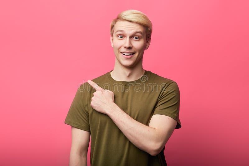 看照相机的快乐的英俊的年轻人,指向手指复制空间 免版税库存照片