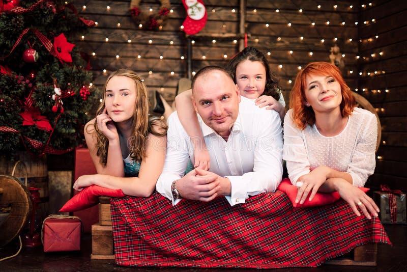 看照相机的愉快的家庭smilingand在圣诞树附近 被修饰的射击 免版税库存照片