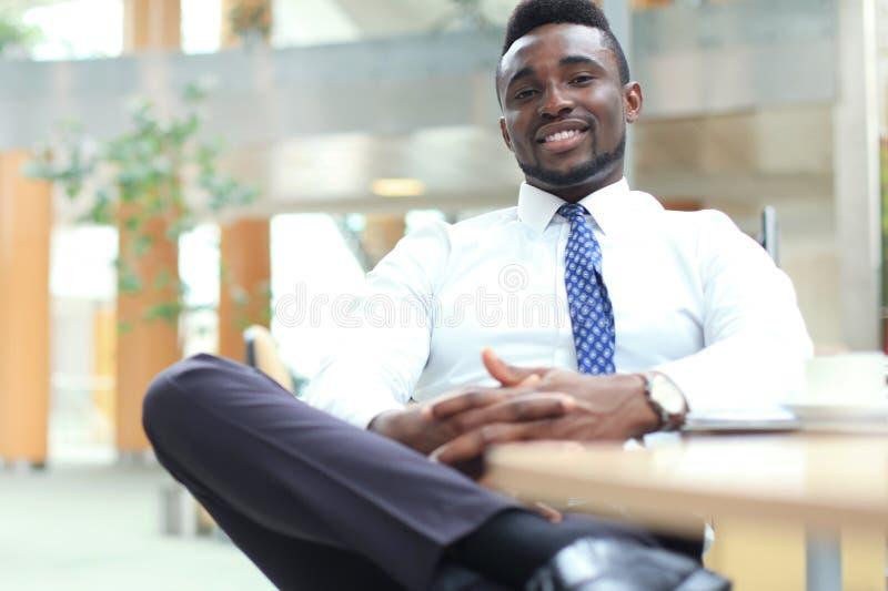 看照相机的愉快的年轻非裔美国人的商人工作场所在办公室 库存照片