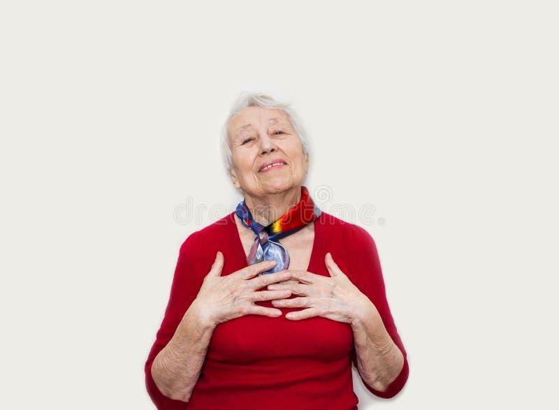 看照相机的愉快的微笑的退休的资深妇女隔绝在白色背景 库存照片