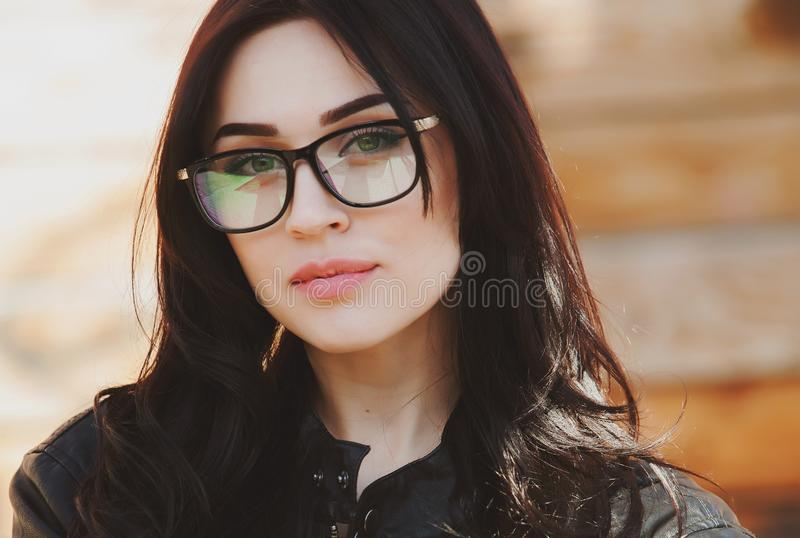 看照相机的时髦玻璃的美丽的正面时兴的时髦的现代深色的女孩 库存照片