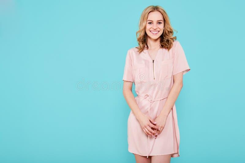 看照相机的桃红色夏天礼服的美丽的微笑的时髦十几岁的女孩 有吸引力的少妇演播室画象 免版税库存图片