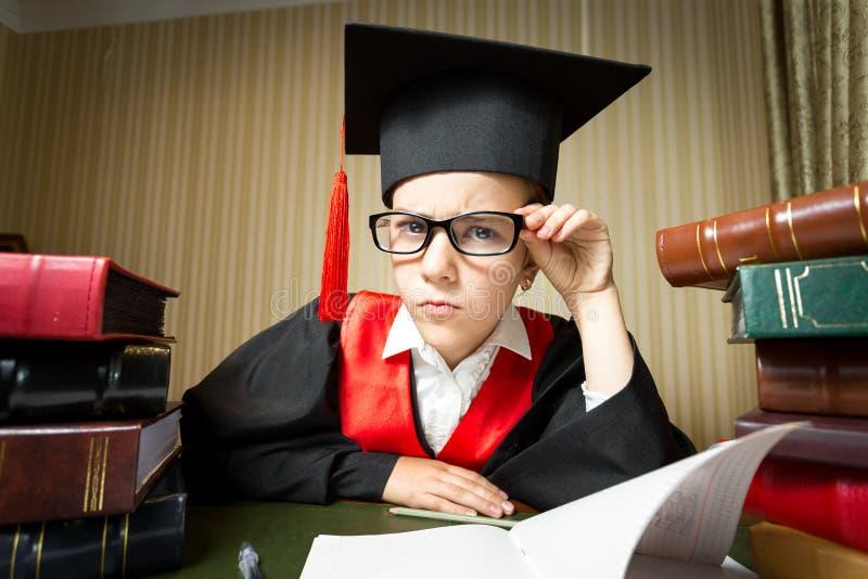看照相机的毕业盖帽和镜片的滑稽的女孩 库存照片