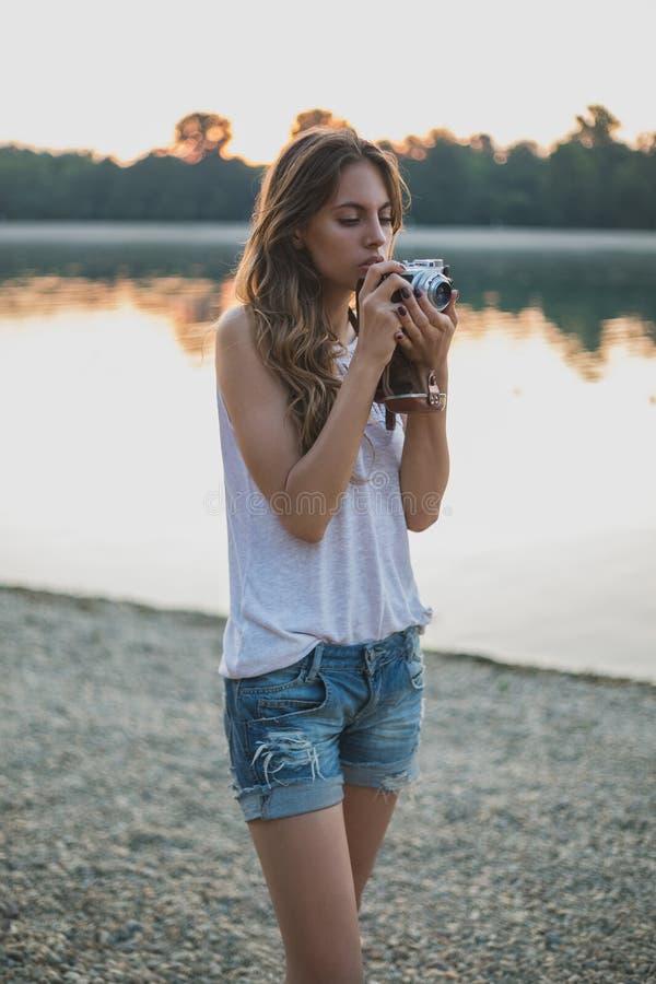 看照相机的海滩的女孩 库存图片