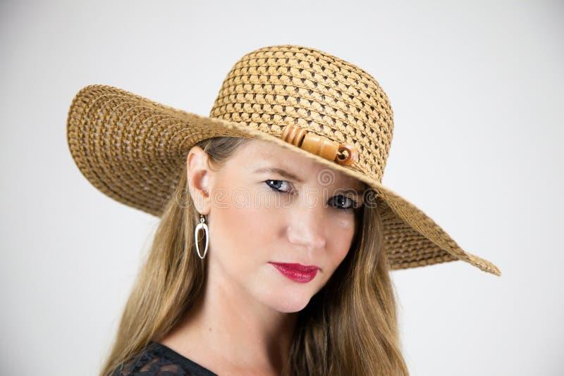 看照相机的特写镜头画象成熟白肤金发的女性大帽子 免版税图库摄影