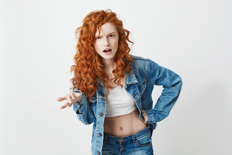 看照相机的生气的残酷红头发人女孩不了解在白色背景 复制空间 库存图片