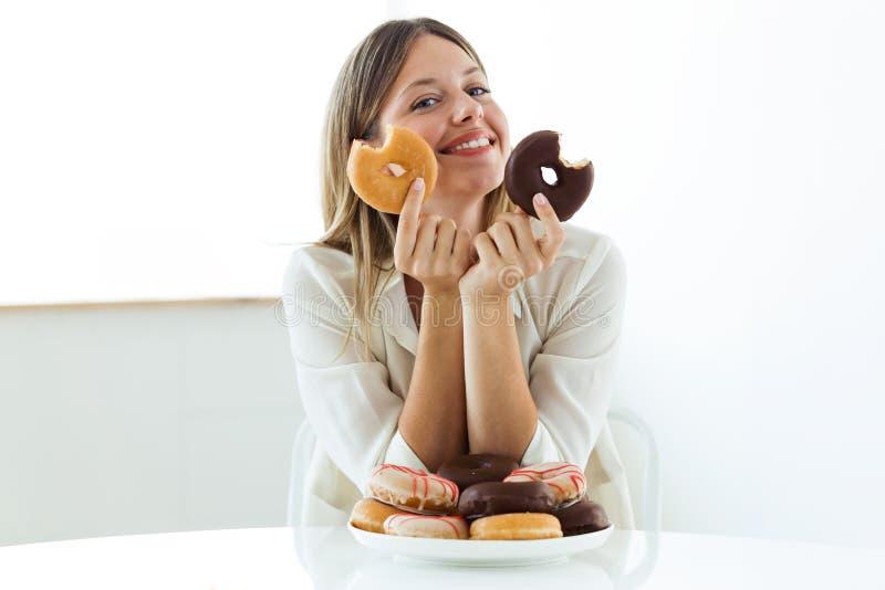 看照相机的美丽的少妇,当在家时吃油炸圈饼 免版税库存图片