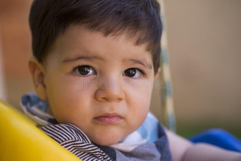 看照相机的美丽的巴西男婴 严重的婴孩 免版税库存照片