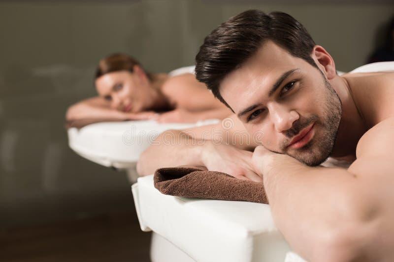看照相机的美好的年轻夫妇,当有按摩在温泉时 图库摄影