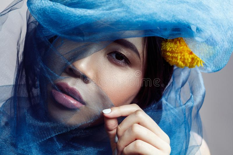 看照相机的肉欲的华美的亚裔妇女画象通过在面孔的蓝色面纱 免版税库存照片