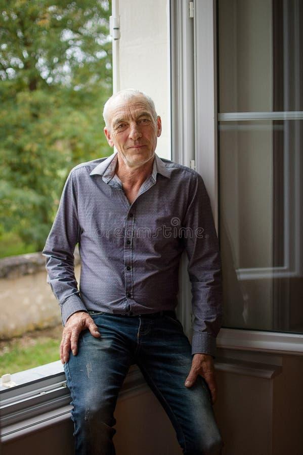 看照相机的英俊的资深灰发的人Portait站立在被打开的窗口前面在他的议院里 库存照片