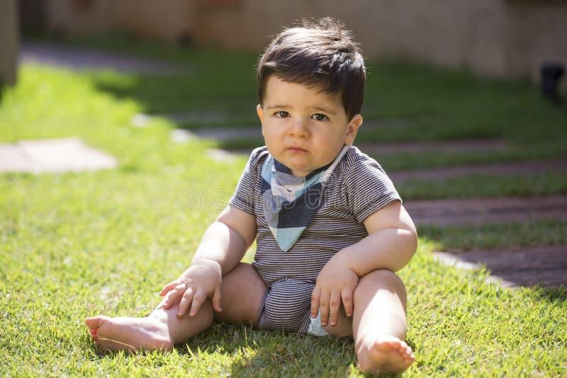 看照相机的草的美丽的巴西男婴 Ser 免版税库存图片