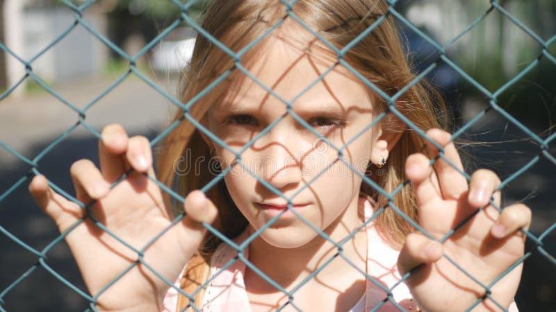 看照相机的被抛弃的,不快乐的离群女孩孩子孤儿的哀伤的沮丧的孩子 免版税库存照片