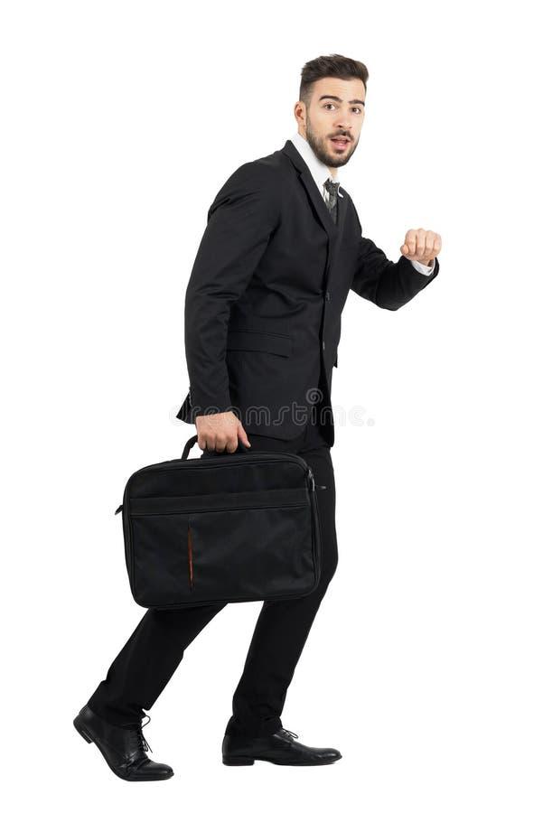 看照相机的跑的惊奇的商人运载的膝上型计算机盒侧视图 免版税库存图片