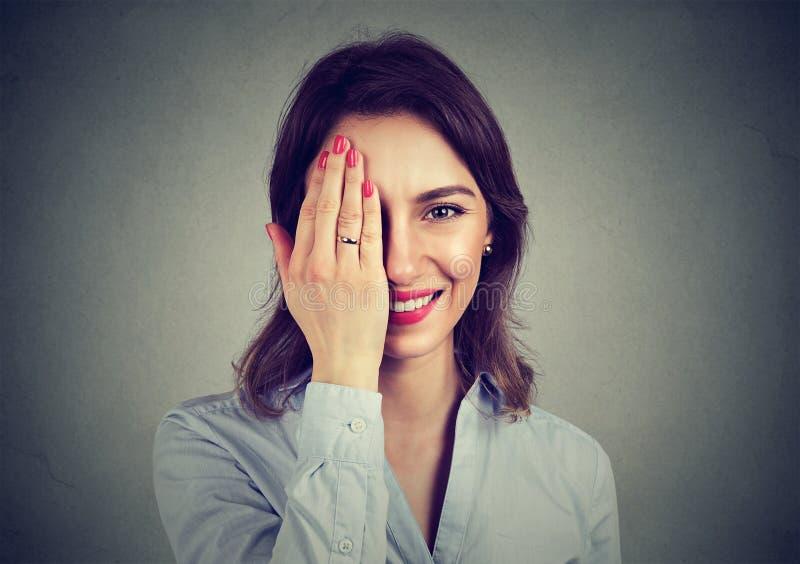 看照相机的逗人喜爱的害羞的妇女 免版税库存图片