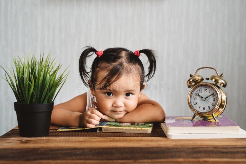 看照相机的逗人喜爱的矮小的亚裔小小孩女孩,当读与闹钟时的书 免版税库存照片