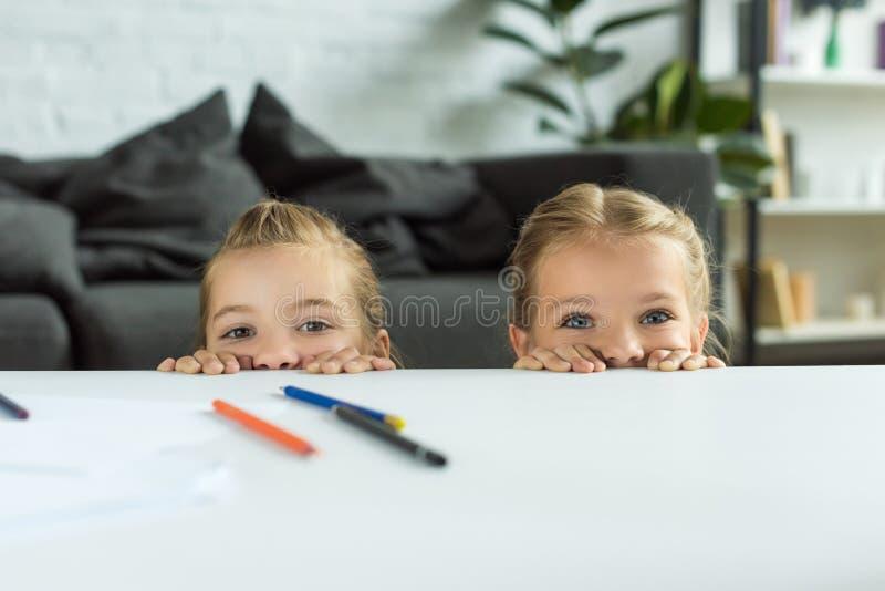看照相机的部份观点的小孩,当掩藏在与铅笔时的桌后 免版税库存图片