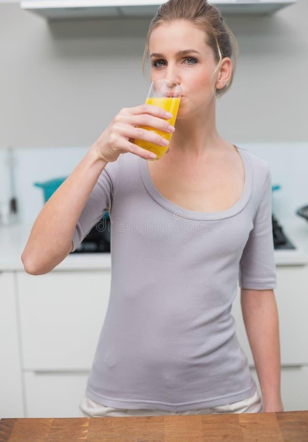 看照相机的镇静华美的模型喝橙汁 免版税库存照片