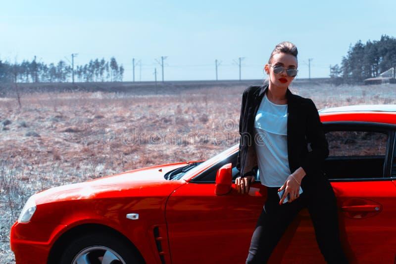 看照相机的镜子太阳镜的年轻魅力夫人在红色跑车附近 库存照片