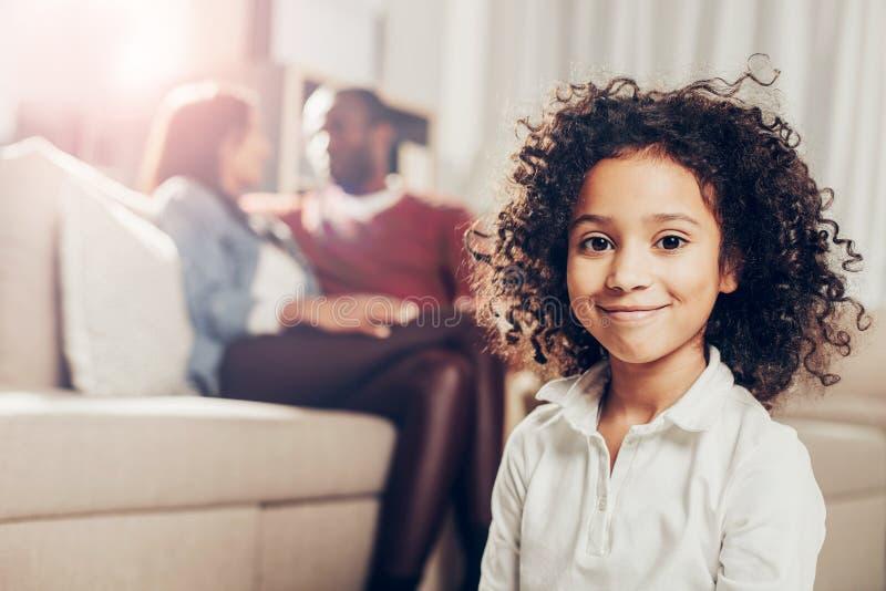 看照相机的高兴的孩子,当父母坐沙发时 免版税库存照片