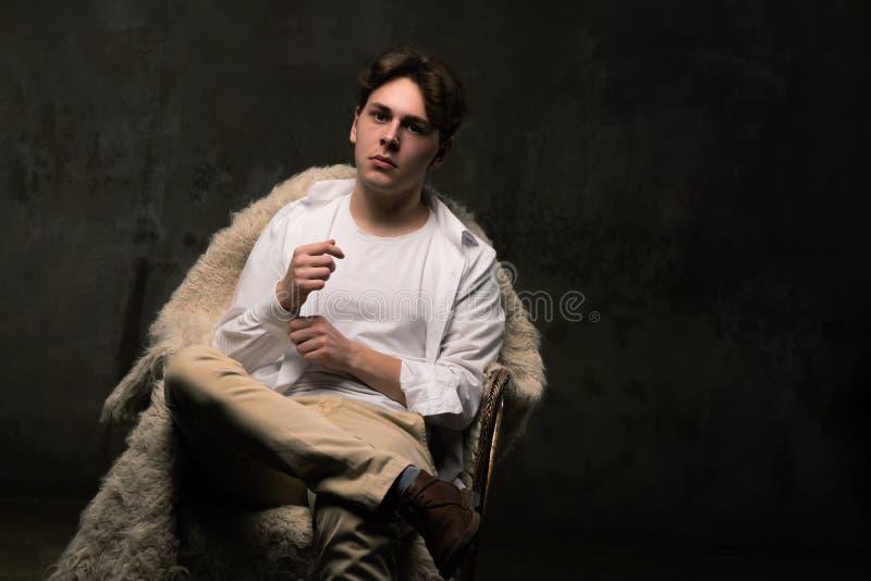 看照相机的黑背景的英俊的年轻人 图库摄影