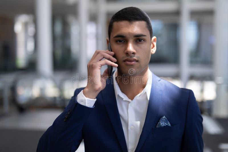 看照相机的Youmg mixed-race商人,当使用手机在现代办公室时 库存照片