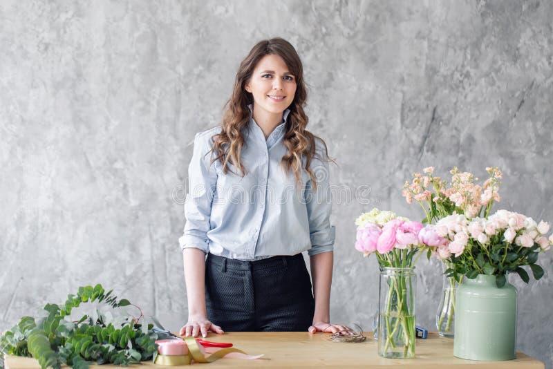 看照相机,卖花人的少妇创造美丽的花束在花店 工作在花店 女孩 库存照片