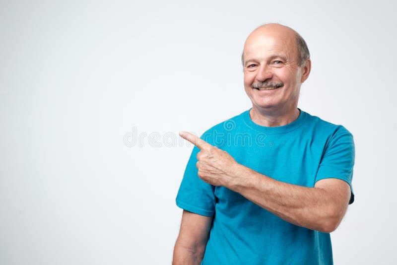 看照相机,微笑和指向在旁边用手的蓝色T恤杉的愉快的老人 免版税库存图片