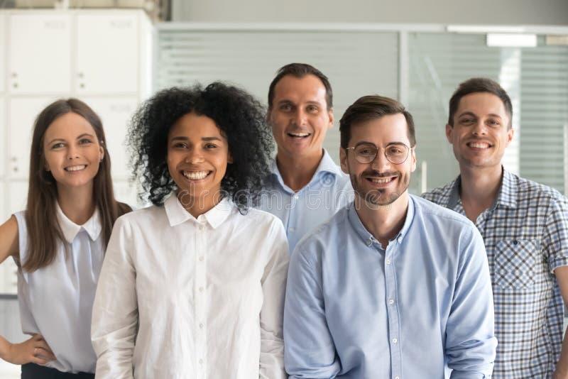 看照相机,队的愉快的多种族专业雇员 免版税库存照片