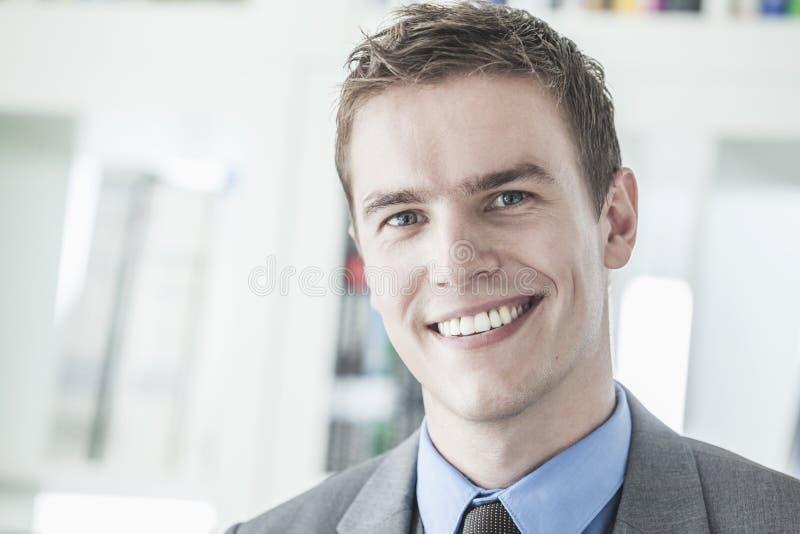 看照相机,首肩的年轻微笑的商人画象  免版税图库摄影