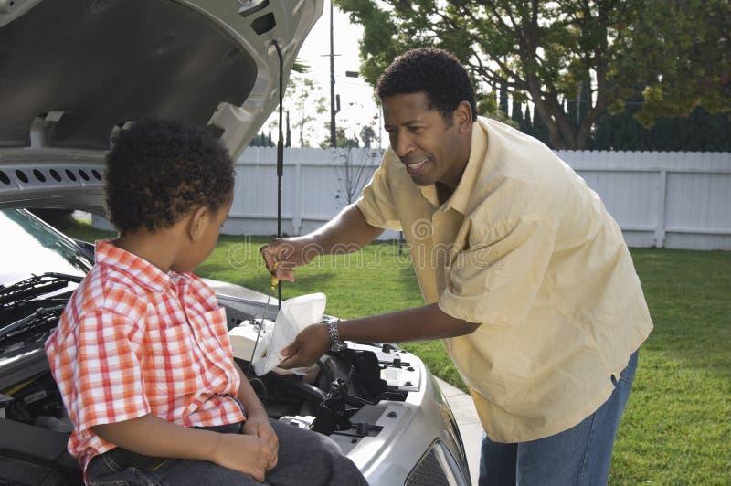 看父亲的男孩检查机器润滑油 免版税库存图片