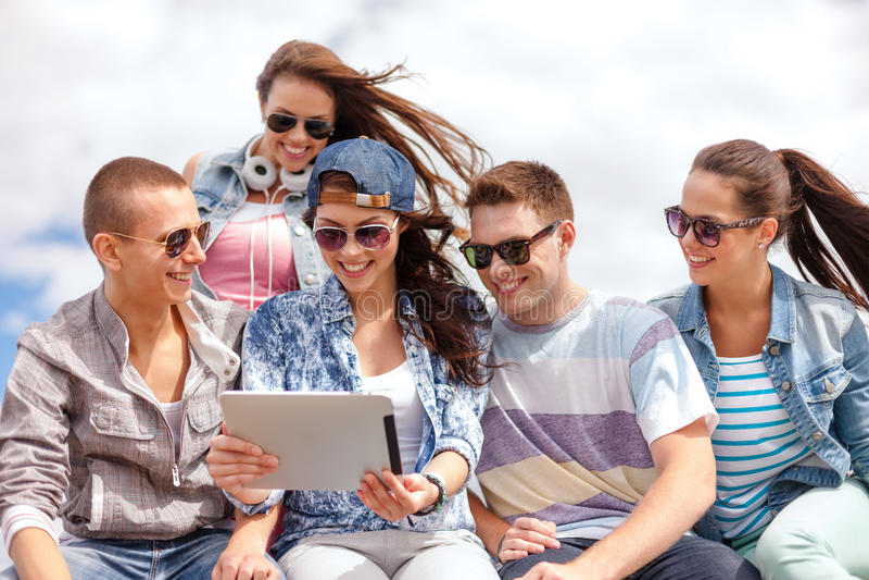 看片剂个人计算机的小组微笑的少年 库存图片