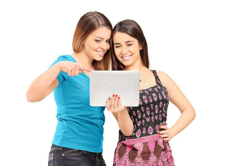 看片剂的两个十几岁的女孩 免版税库存照片