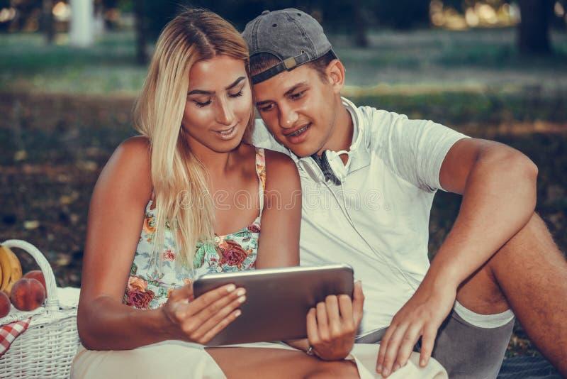 看片剂的射击一对愉快的年轻夫妇,当有野餐时 免版税库存图片