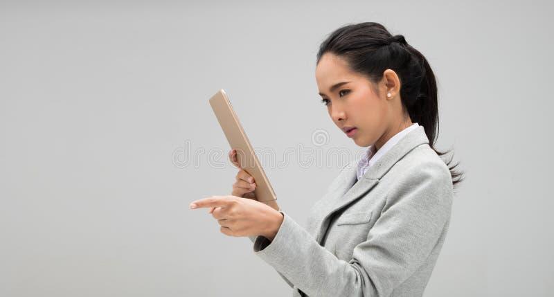 看片剂的年轻女商人正装 图库摄影