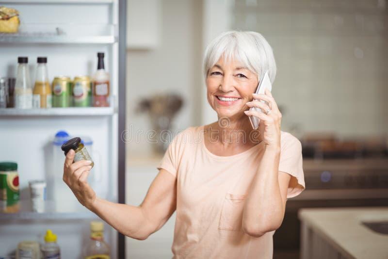 看瓶子的资深妇女,当谈话在手机在厨房里时 免版税库存照片