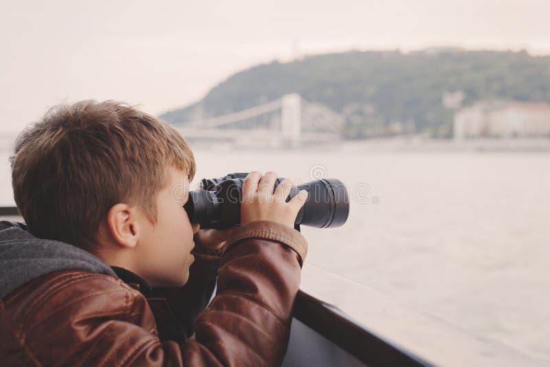 看由双筒望远镜的小男孩在多瑙河,布达佩斯的旅行期间 库存照片