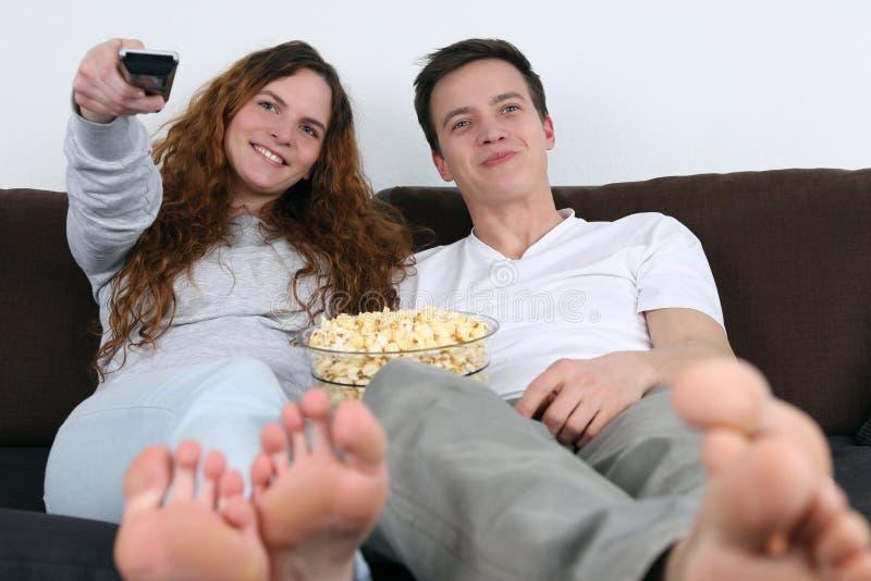 看电视和吃玉米花的年轻夫妇 免版税库存照片