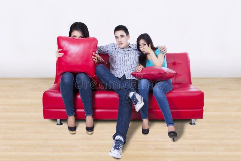 看电视的三个年轻朋友 免版税库存图片