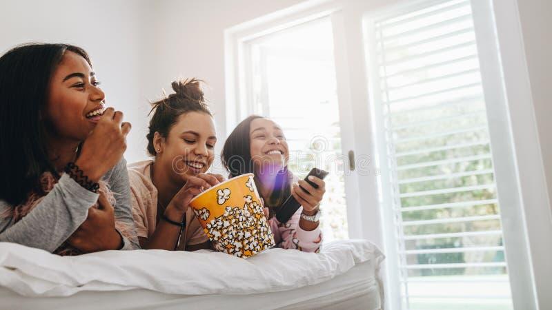 看电视的女孩说谎在吃玉米花的床上 免版税库存图片
